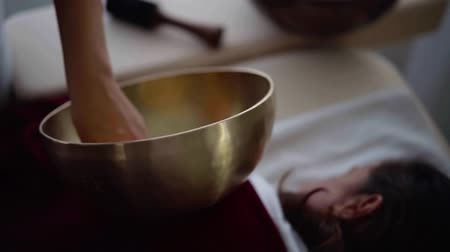 Close-up shot of a female massage therapist playing singing bowl on womans back.