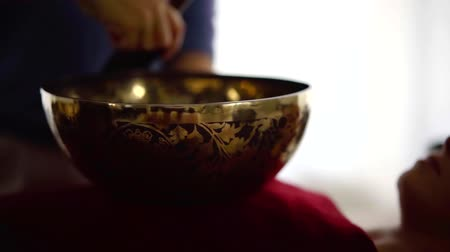 Close up shot of woman playing on a traditional tibetan bronze singing bowl.