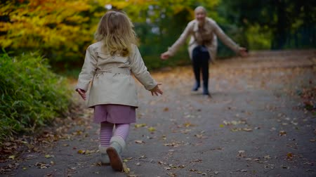 мама : Shot from behind of a cute little girl happily running to her mother in park.