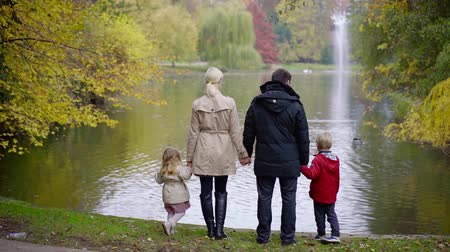 Back view of a strong lovely family standing on a shore of a pond and looking at water, family outdoor in a park.