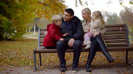 Family couple with two kids sitting peacefully on a bench in city park, fall season.