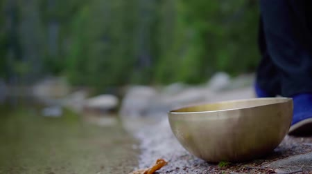 singing bowl : Woman takes a bronze singing bowl from a pond shore in a park. Stock Footage