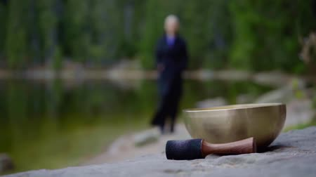 Focus on tibetan singing bowl on a shore, blurred woman walking along lake shore outdoor.