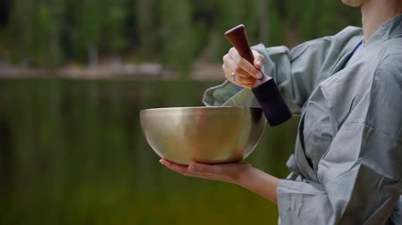 Close-up shot of a female monk playing tibetan singing bowl out in nature by big lake.
