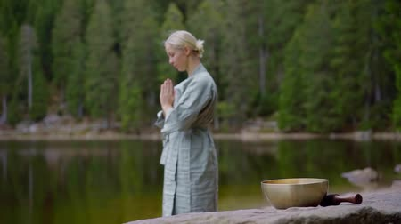 Outdoor shot of a woman in blue apparel meditating in a forest by the lake.