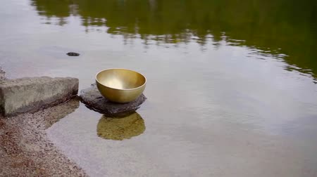 Beautiful tibetan bronze bowl in a forest on a small rock on lake shore. Stock mozgókép