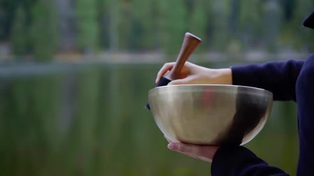 consciente : Close up shot of a woman playing a tibetan singing bowl outdoor in nature by the lake. Vídeos