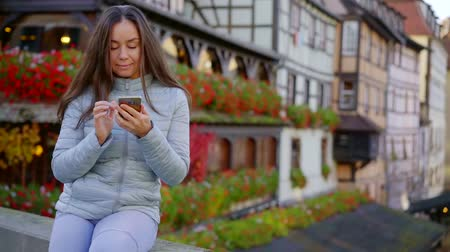 Lovely brunette girl sitting with smartphone outdoor in europe.