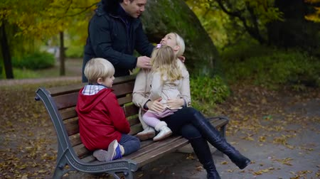 autumnal : Father coming to his family in the park. Stock Footage