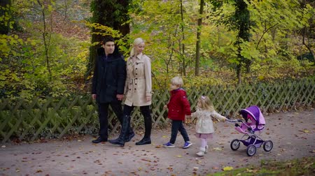Couple with kids spending weekend day in beautiful autumn park.