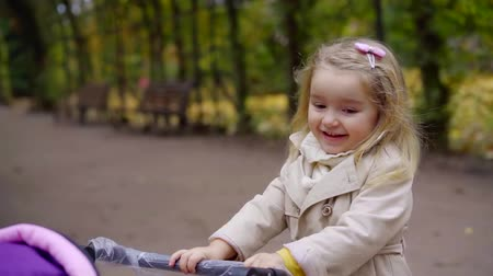Portrait of a cutest blonde child with pink stroller smiling and playing in park. Stock mozgókép