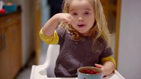 Cute kid eating sweet berries from a bowl in home kitchen. Stock mozgókép