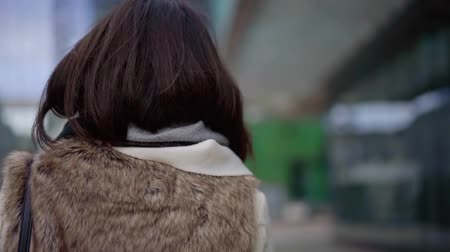 Shot from behind of a charming girl in a fur vest casually walking in big city alone.