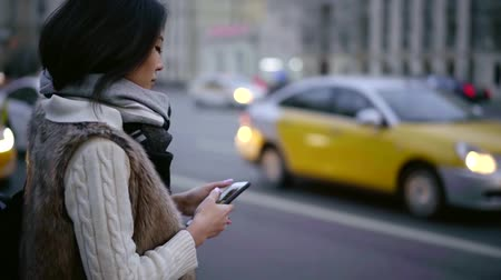 Brunette firl standing by the road with a smartphone and ordering a taxi. Stock mozgókép
