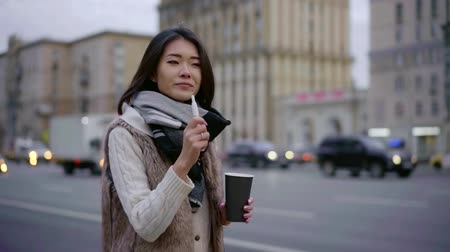 Cute brunette girl walking in a city in stylish outfit with a cup of coffee and smoking iqos.