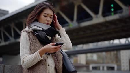 Attractive urban girl using smartphone outdoor wearing fashionable clothes.