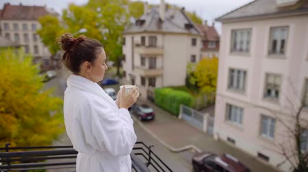 Beautiful smiling woman enjoying european city view on breakfast from balcony.