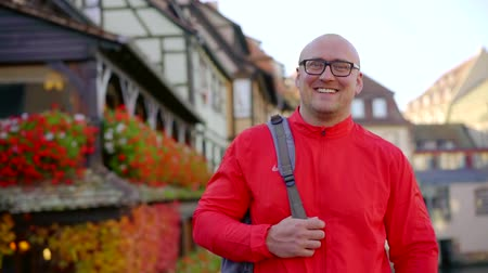 Happy smiling bald man with backpack outdoor in city in fall, great day.