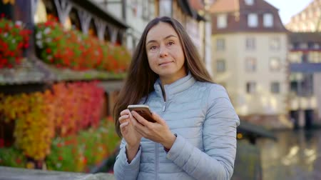Charming smiling brunette woman with smartphone outdoor in autumn.