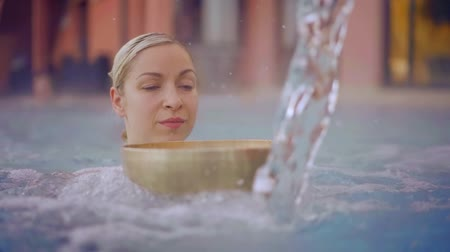 Portrait of a relaxed blonde woman in a pool warm pool with a tibetan bowl. Stock mozgókép