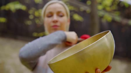Portrait of blonde woman playing bronze tibetan singing bowl in nature.