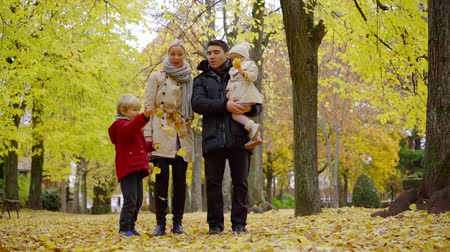 Father mother and two children enjoying lovely family walk in autumn park. Stock mozgókép