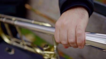 Close-up shot of a musician taking his brass intrument and preparing to play song outdoor in park.