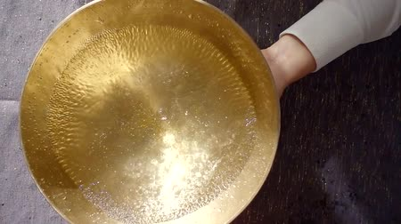 himalaia : human is striking on copper nepal bowl with water for nada therapy and healing by sound Stock Footage