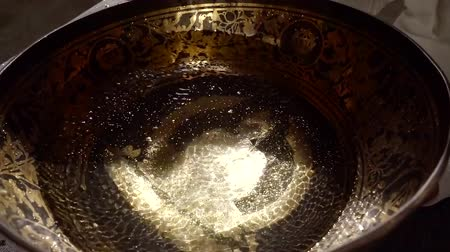 átlyukasztás : water is vibrating inside copper bowl in nada therapy session, oscillations is making sound Stock mozgókép