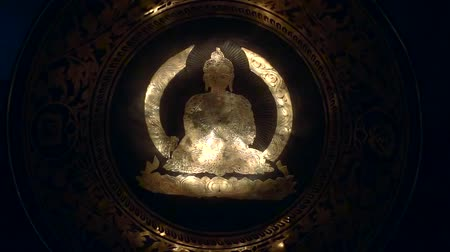 relics : blazing lights are illuminating drawing image of buddha inside metal bowl, in old Buddhist temple