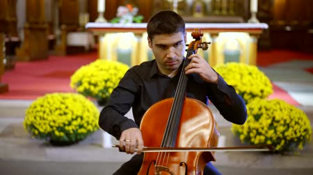 виолончель : adult man is playing contrabass in catholic church in funeral day, solo of one classical instrument
