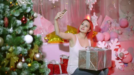 christmas tree with lights : charming girl is taking selfie by camera of smartphone, sitting with big gift box in new year holiday