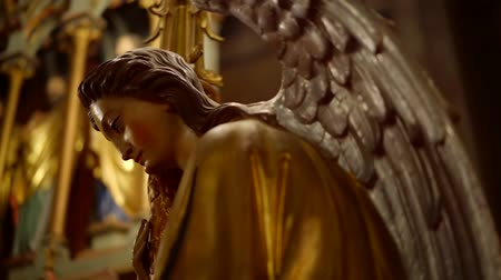 alado : gilded statue of angel with large wings in a catholic church, close-up view, camera moving around