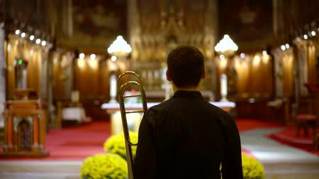 brazen : male trumpeter is standing in front of altar in church and playing trumpet, performing a concert