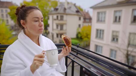 croissants : Lovely woman eating on balcony in the morning on balcony, looking at the city while eating. Stock Footage