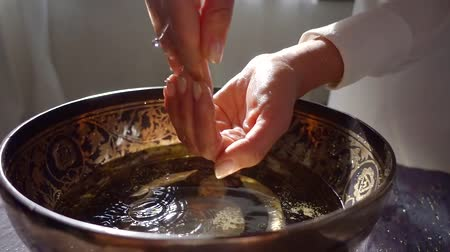 dourado : woman is washing hands over old traditional indian bowl with patterns, water is pouring from up