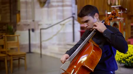 виолончель : emotional male cellist is playing in church hall, performing dramatic classical music, moving bow Стоковые видеозаписи
