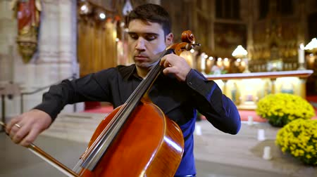 rehearsing : adult man is playing cello in christian church, performing composition on a concert for parishioners Stock Footage