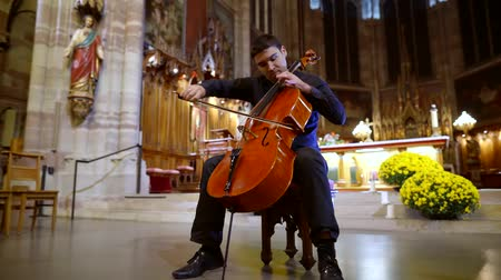 acoustic : adult man musician is playing violoncello in a church hall in front of altar, sitting on chair