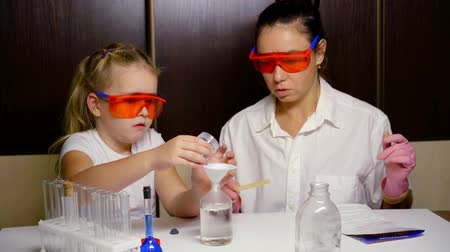 analyzes : woman is reading instruction for chemical set and little girl is helping, perform experiment Stock Footage