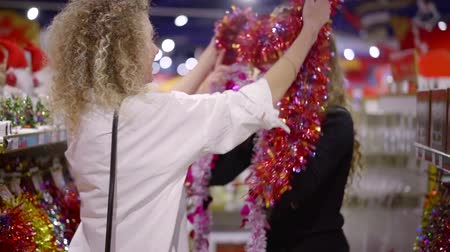 cicili bicili : two happy women are putting on each other shiny decorative tinsel in a store, laughing in christmas Stok Video