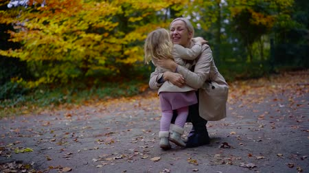 atender : Adorable daughter running fast to her mother to hug her outdoor in a park.