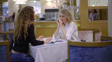 rodzeństwo : two young women are sitting in restaurant in daytime and communicating, talking and chatting