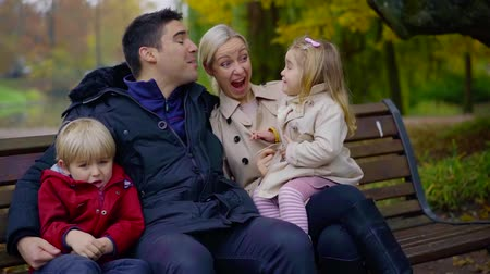 bank : Portrait of a big happy family on park bench in autumn, spending time together, storng bond.