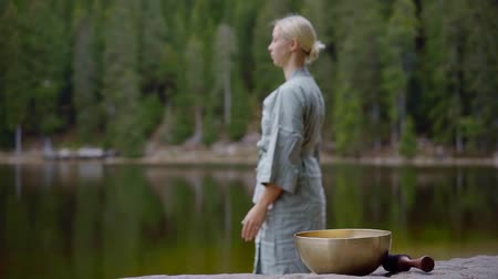 singing bowl : Blurred blonde woman standing by the lake in forest and meditating, singing bowl lying on a rock. Stock Footage