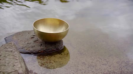 none : Traditional tibetan singing bowl on a rock in lake.