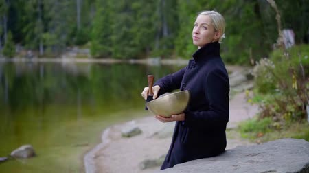singing bowl : Blonde woman in black dress sitting on a pond shore with a tibetan singing bowl and playing. Stock Footage