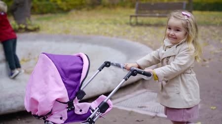 wozek dzieciecy : Beautiful little girl is playing with a doll in a stroller.