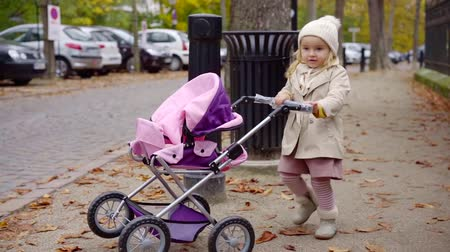 sáně : Cute little girl playing with small pink stroller outdoor in fall.
