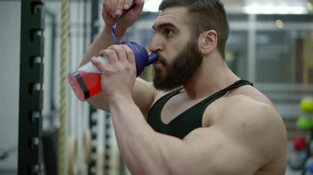 diluted : brutal muscular man with a beard drinks dilute amino acids from a shaker during training Stock Footage
